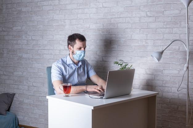 Jonge man met medische gezichtsmasker op het werk vanuit huis als gevolg van een uitbraak van het coronavirus met laptop