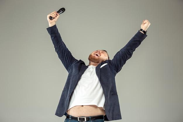 Jonge man met microfoon op grijs, leidend met microfoon