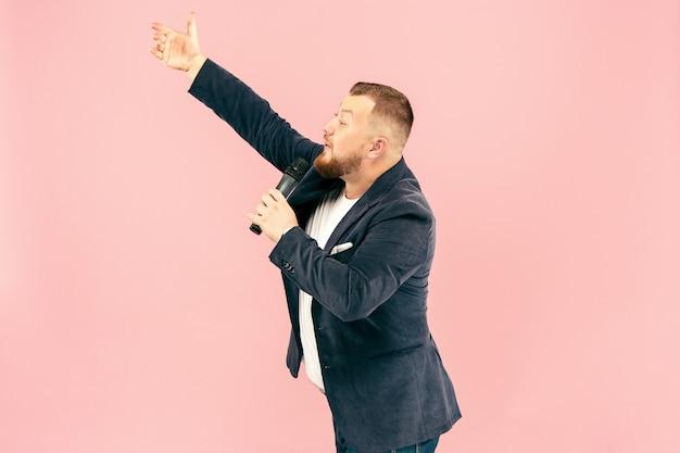 Jonge man met microfoon op roze ruimte, leidend met microfoon