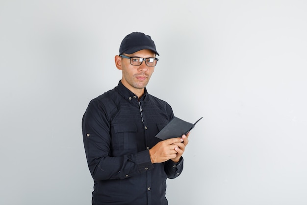 Jonge man met mini-notebook in zwart shirt en pet