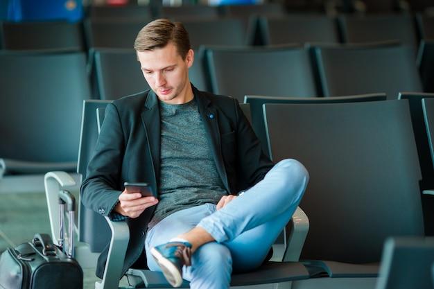 Jonge man met mobiel op de luchthaven tijdens het wachten op instappen.