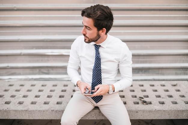 Jonge man met mobiel wegkijken