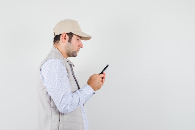 Jonge man met mobiele telefoon bij de hand in beige jasje en pet en serieus kijken. vooraanzicht.