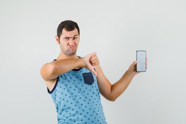 Jonge man met mobiele telefoon, duim omlaag in blauw hemd en op zoek naar ontevredenheid