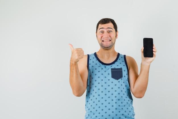 Jonge man met mobiele telefoon, duim opdagen in blauw hemd en op zoek gelukkig
