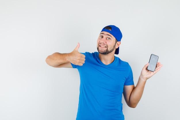 Jonge man met mobiele telefoon met duim omhoog in blauw t-shirt en pet en op zoek tevreden