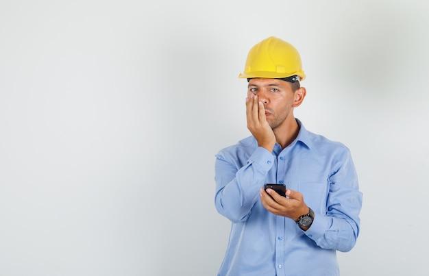 Jonge man met mobiele telefoon met hand op mond in shirt