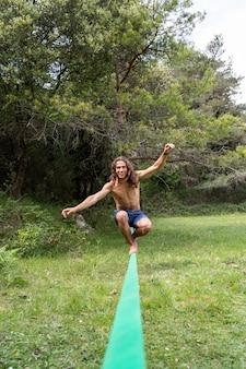 Jonge man met naakte torso balanceren op slackline in groen veld op zomer