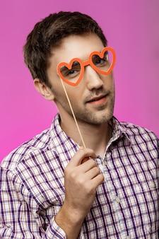 Jonge man met nep-bril over paarse muur. verjaardagsfeest.