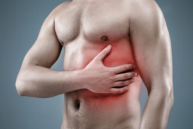 Jonge man met niked torso met hartaanval op grijze studio achtergrond