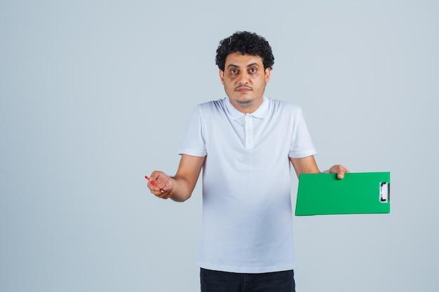 Jonge man met notitieboekje en pen, schouders ophalend in wit t-shirt en spijkerbroek en peinzend kijkend. vooraanzicht.