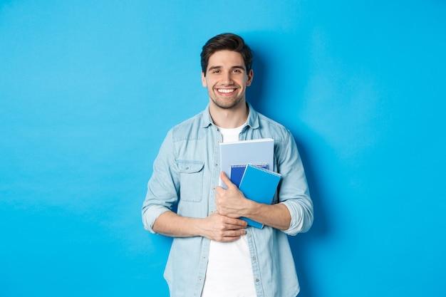 Jonge man met notitieboekjes en studiemateriaal, gelukkig glimlachend, staande over blauwe achtergrond