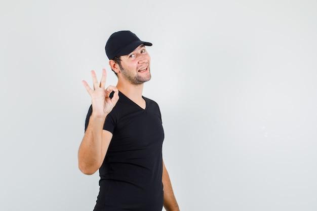 Jonge man met ok teken in zwart t-shirt, pet en op zoek vrolijk.