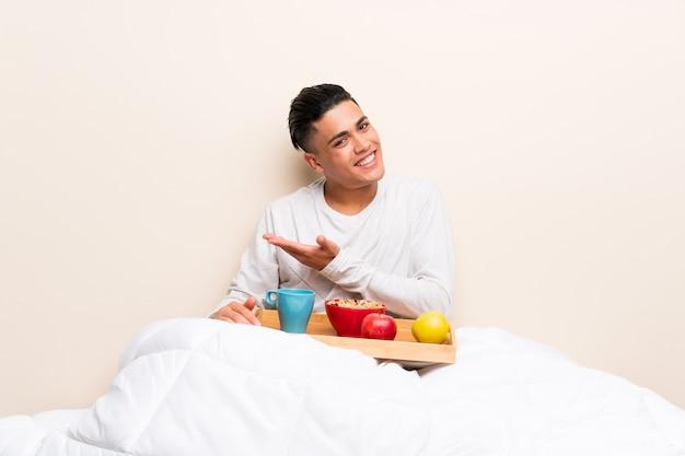 Jonge man met ontbijt in bed uitbreiding van de handen aan de zijkant voor het uitnodigen om te komen