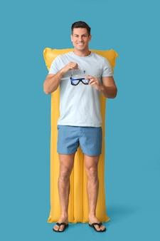 Jonge man met opblaasbare matras en snorkelmasker