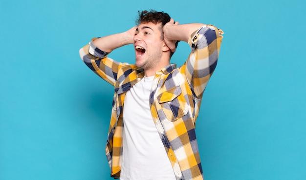 Jonge man met open mond, geschokt en geschokt op zoek naar aanleiding van een vreselijke fout, handen naar het hoofd verheven Premium Foto
