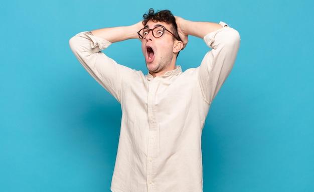 Jonge man met open mond, geschokt en geschokt op zoek naar aanleiding van een vreselijke fout, handen naar het hoofd verheven