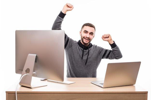 Jonge man met opgeheven vuisten met behulp van laptop en personal computer aan geïsoleerde tafel op wit