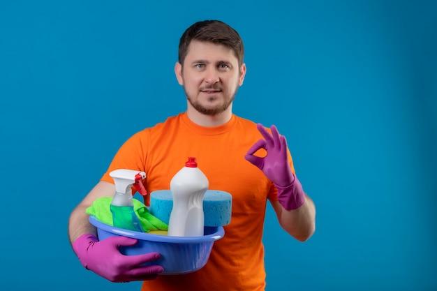 Jonge man met oranje t-shirt en rubberen handschoenen met bekken met reinigingsgereedschap