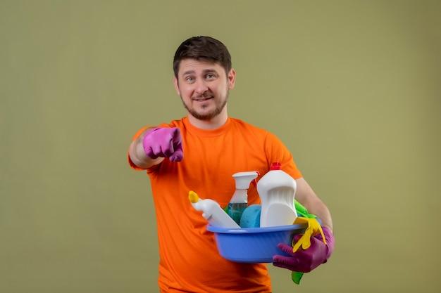 Jonge man met oranje t-shirt en rubberen handschoenen met bekken met schoonmaakgereedschap glimlachend positief en blij wijzend met vinger naar camera staande over groene muur 2
