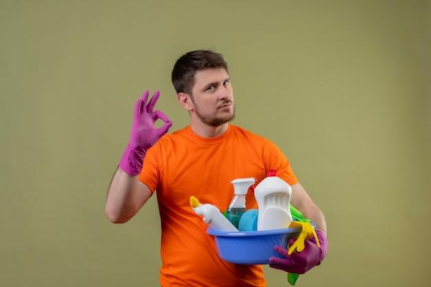 Jonge man met oranje t-shirt en rubberen handschoenen met bekken met schoonmaakkosten op zoek zelfverzekerd doen ok teken staande over groene pagina