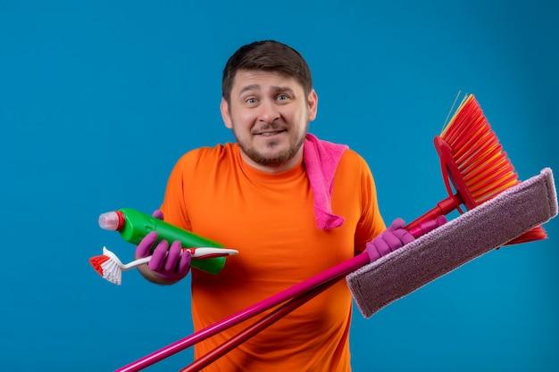 Jonge man met oranje t-shirt en rubberen handschoenen met reinigingsgereedschap