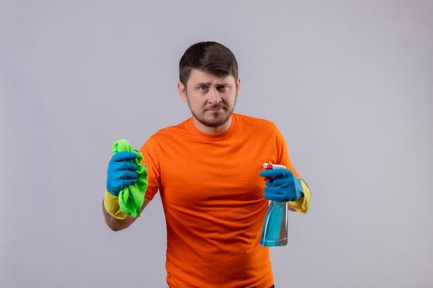 Jonge man met oranje t-shirt en rubberen handschoenen met reinigingsspray en deken ontevreden
