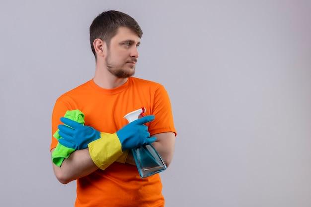 Jonge man met oranje t-shirt en rubberen handschoenen met reinigingsspray en deken staande met gekruiste armen