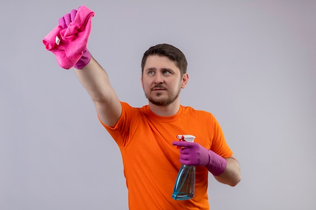 Jonge man met oranje t-shirt en rubberen handschoenen met reinigingsspray en tapijt te kijken