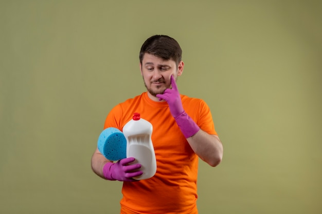 Jonge man met oranje t-shirt en rubberen handschoenen met schoonmaakbenodigdheden en spons te kijken met peinzende uitdrukking op gezicht denken staande over groene muur