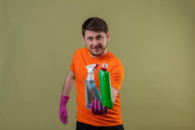 Jonge man met oranje t-shirt en rubberen handschoenen met schoonmaakbenodigdheden glimlachend blij en positief staande over groene muur 3