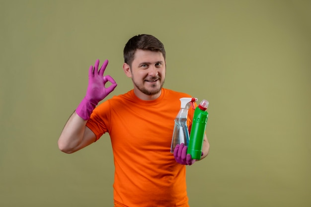 Jonge man met oranje t-shirt en rubberen handschoenen met schoonmaakbenodigdheden glimlachend gelukkig en positief doen ok teken staande over groene muur