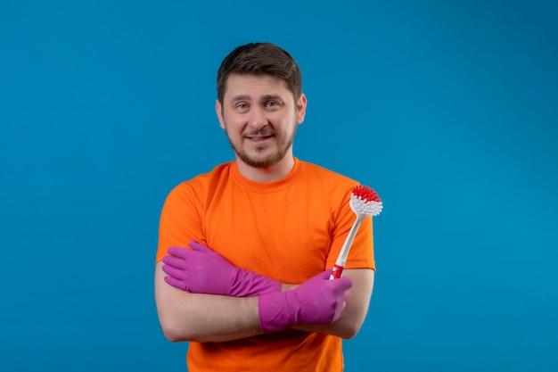 Jonge man met oranje t-shirt en rubberen handschoenen met schrobborstel