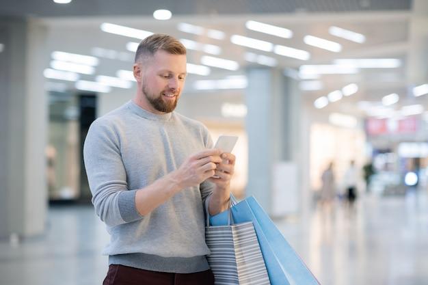 Jonge man met paperbags en smartphone promo op scherm kijken of scrollen door online winkelpagina's terwijl hij in het winkelcentrum staat