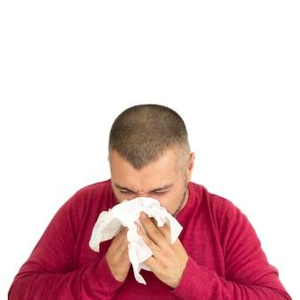 Jonge man met papieren zakdoek en niezen geïsoleerd op een witte achtergrond