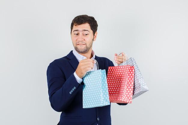Jonge man met papieren zakken in blauw pak en op zoek nieuwsgierig, vooraanzicht.