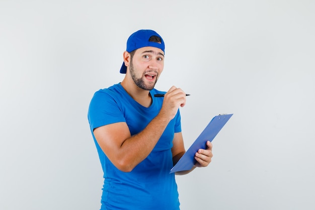 Jonge man met pen en klembord in blauw t-shirt en pet