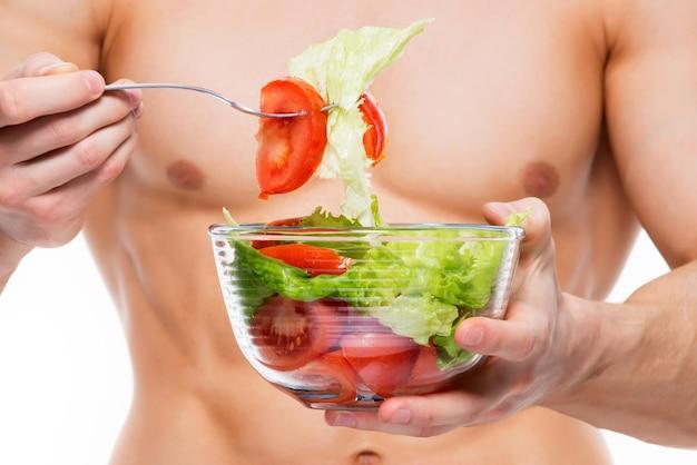 Jonge man met perfect lichaam houdt salade - geïsoleerd op een witte muur.