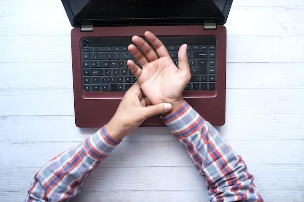 Jonge man met pijn in de pols tijdens het werken op een laptop