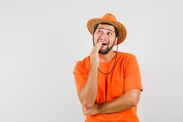 Jonge man met pijnlijke tand in oranje t-shirt, hoed en ongemakkelijk, vooraanzicht.