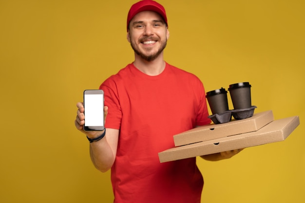 Jonge man met pizza en smartphone geïsoleerd op gele muur