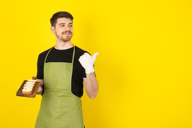 Jonge man met plakjes cake en wijzende vinger weg.