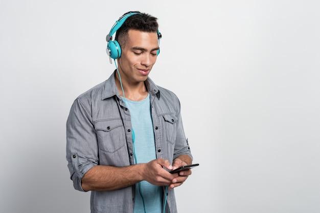 Jonge man met plezier luisteren naar muziek in de oortelefoons en kijken naar het scherm van de telefoon