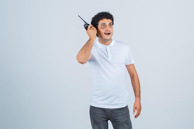 Jonge man met politie walkie talkie telefoon in wit t-shirt, broek en verbaasd kijken. vooraanzicht.