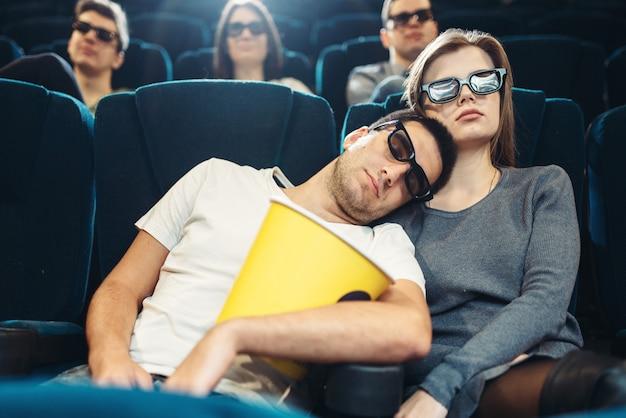 Jonge man met popcorn slapen in de bioscoop. saai filmconcept, mensen kijken naar film