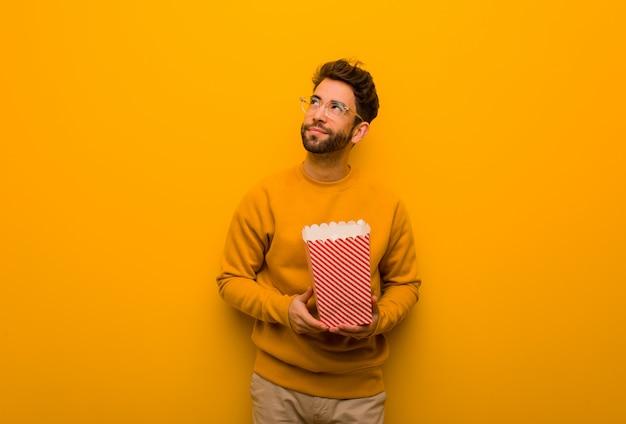 Jonge man met popcorns dromen van het bereiken van doelen en doeleinden