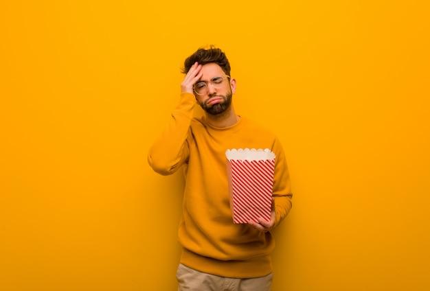 Jonge man met popcorns moe en erg slaperig
