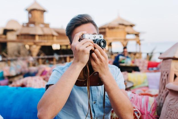 Jonge man met professionele retro camera rusten op terras, vrienden te wachten