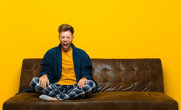 Jonge man met pyjama die agressief schreeuwt, er heel boos, gefrustreerd, verontwaardigd of geïrriteerd uitziet, nee schreeuwend. zittend op een bank