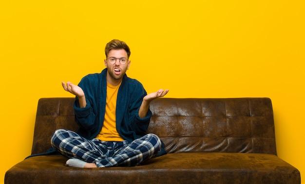 Jonge man met pyjama die zich niet bewust en verward voelt, niet zeker welke keuze of optie hij moet kiezen, zich afvragend. zittend op een bank